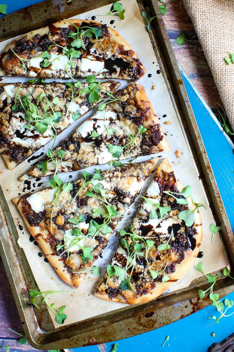 Caramelized onion and gorgonzola flatbread pizza garnished with fresh micro greens