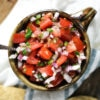 Ceramic bowl filled with homemade pico de gallo loaded with tomatoes onion garlic jalapeno and cilantro