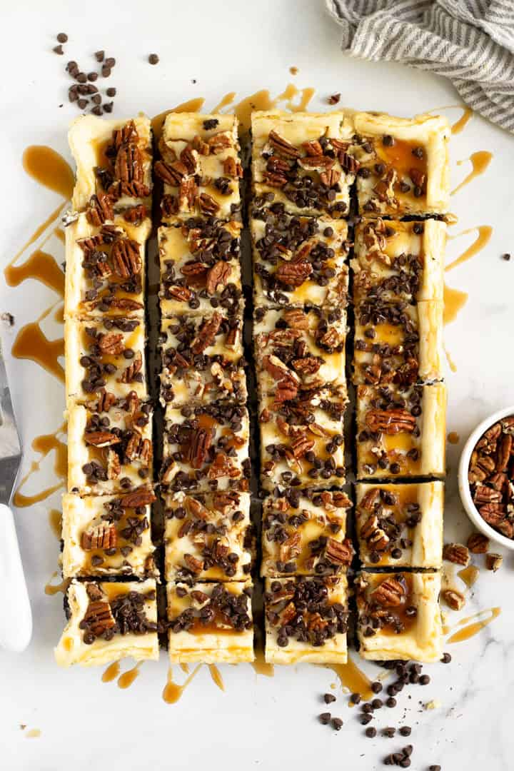 Overhead shot of turtle cheesecake bars cut into squares
