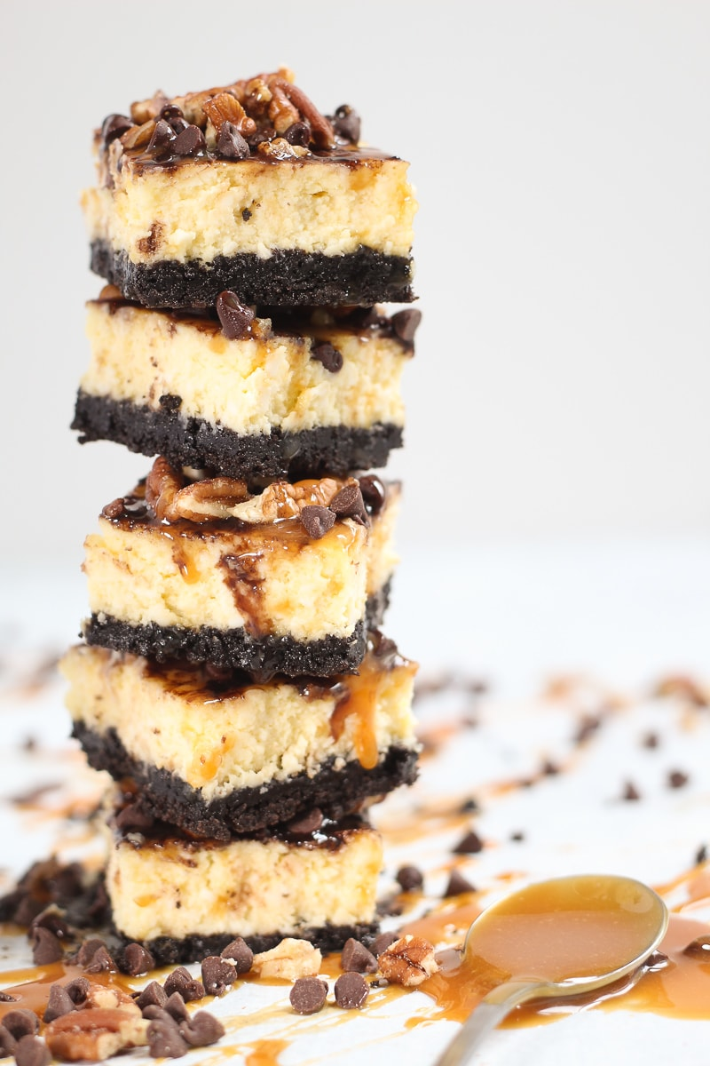 A tower of stacked turtle cheesecake bars loaded with chocolate caramel and pecans