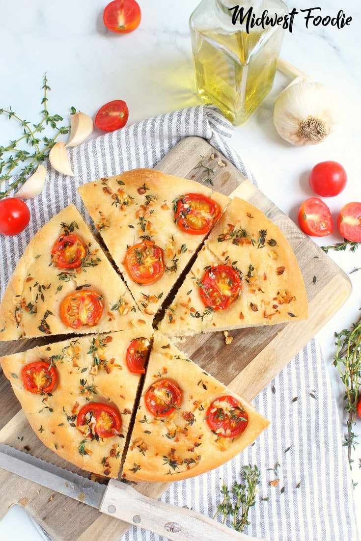 Herb & Tomato Focaccia Bread -- This easy recipe is perfect as an appetizer or works great as a hearty bread for a delicious sandwich! To get the best focaccia bread, drizzle with a generous amount of herb infused olive oil and bake in a pie dish or cast iron skillet. It bakes up crispy on the outside, but super soft on the inside. #midwestfoodie #easy #simple #appetizer #bread #sandwich #castiron #tomato #garlic #herb