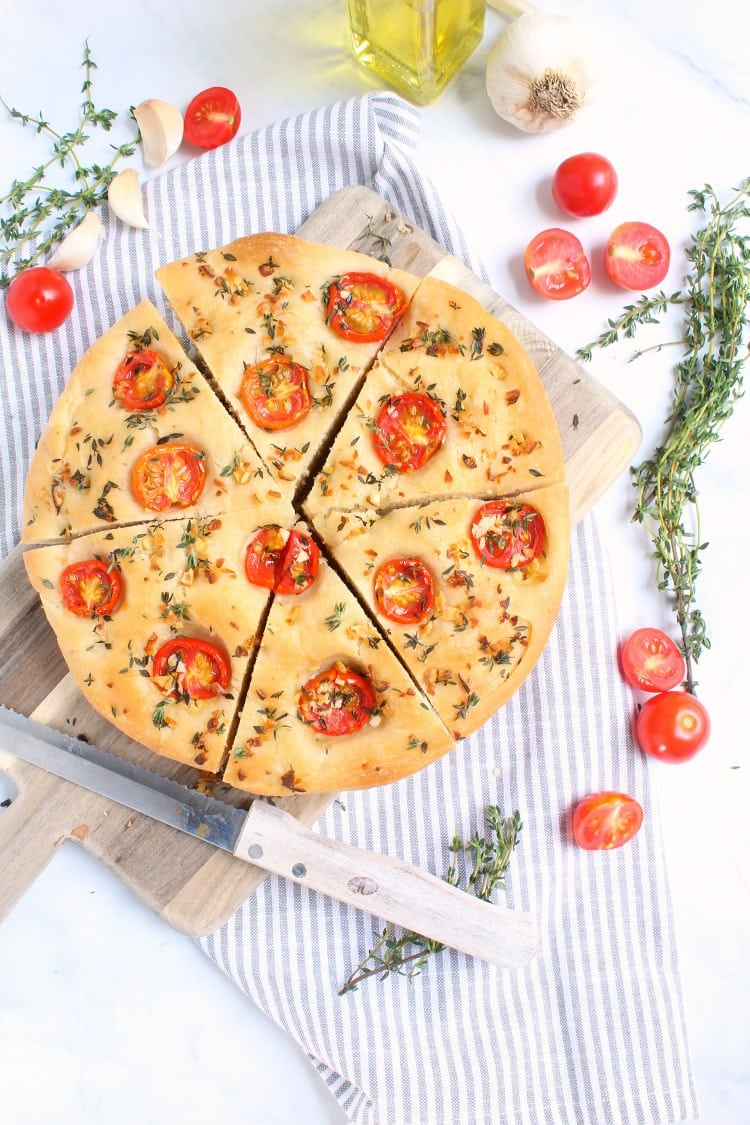 A freshly baked loaf of focaccia bread with garlic herb and tomatoes