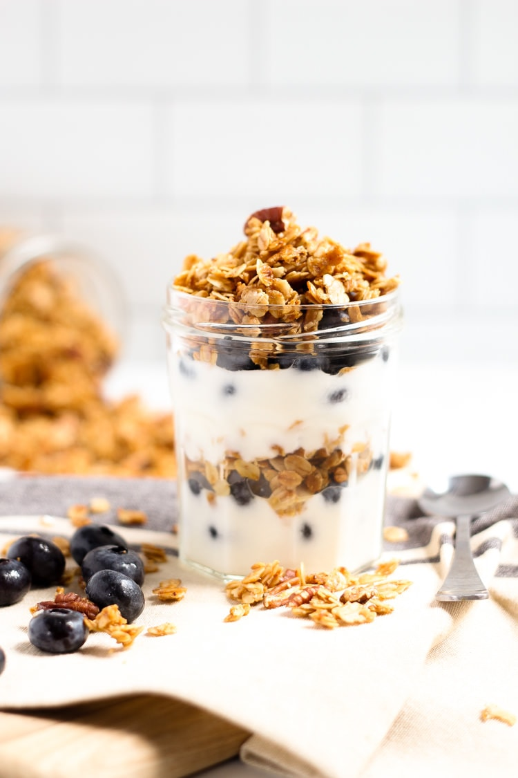 Mason jar filled with yogurt and homemade vegan granola with fresh blueberries