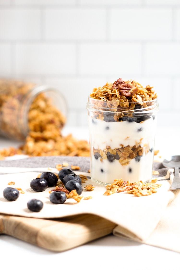 Mason jar filled with yogurt and homemade vegan granola with fresh blueberries