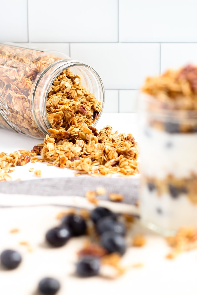 Large mason jar tipped over with homemade vegan granola spilling out onto the counter
