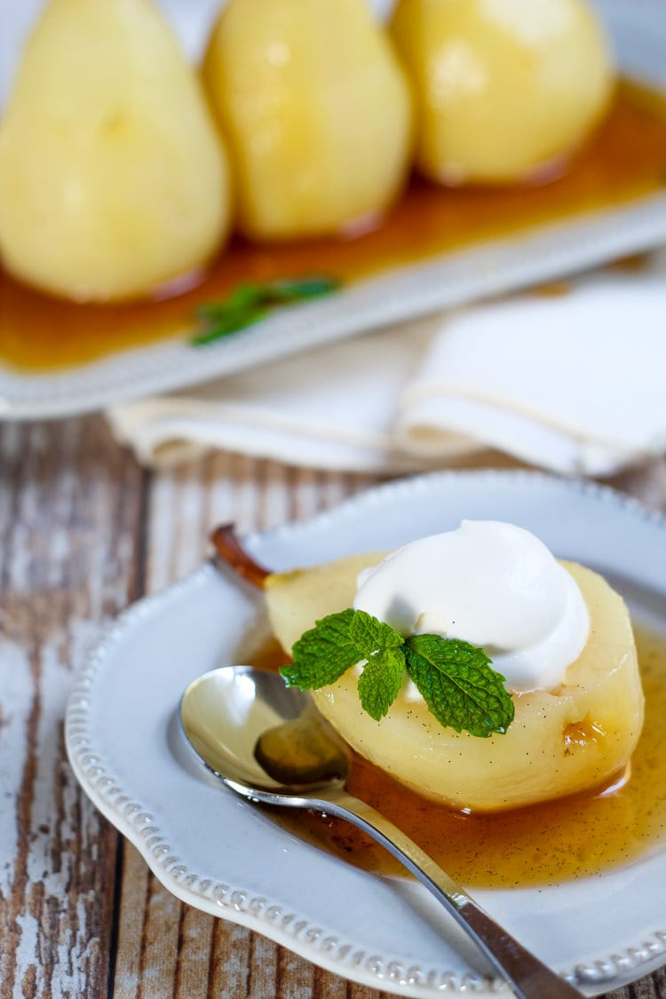Half a poached pear dolloped with homemade whipped cream and garnished with fresh mint leaves