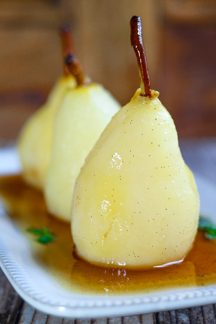 Spiced white wine poached pears on a serving platter