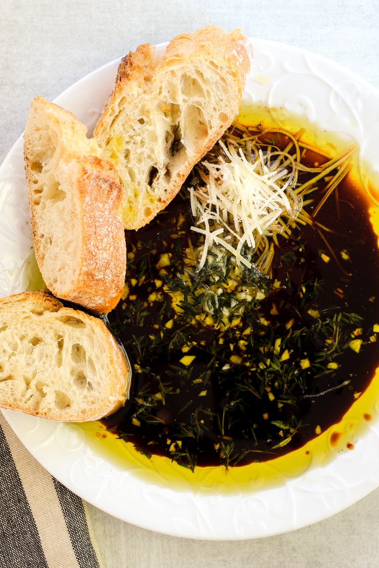 White serving dish filled with olive oil and balsamic vinegar bread dip with crusty sliced baguette on the side