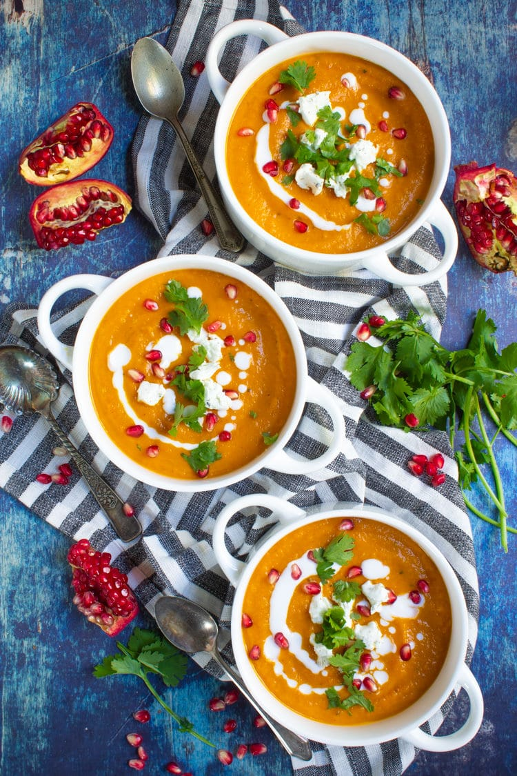 Three hearty bowls of Moroccan roasted veggies soup garnished with goat cheese pomegranate seeds and fresh chopped cilantro