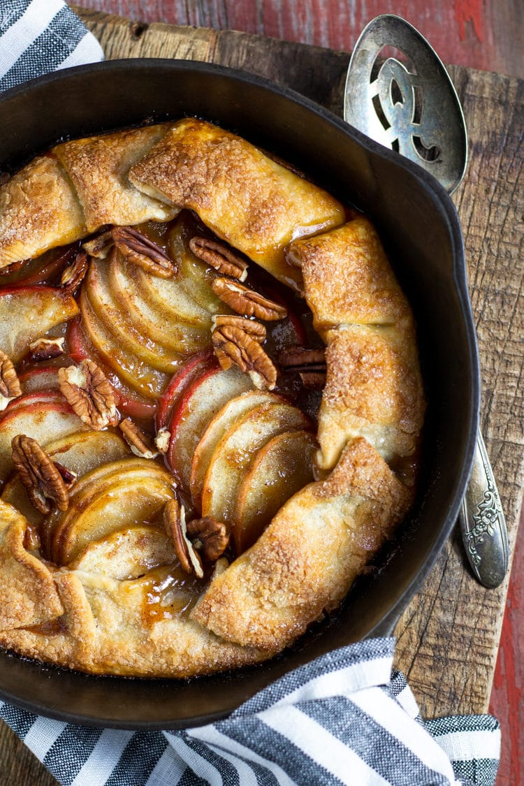 A rustic apple galette baked in a cast iron pan with a serving spoon ready to serve