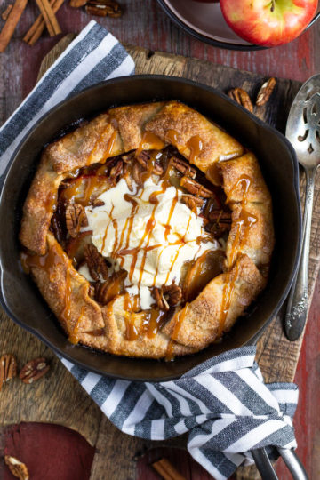 An apple galette baked in a cast iron pan garnished with caramel sauce pecans and a big scoop of ice cream
