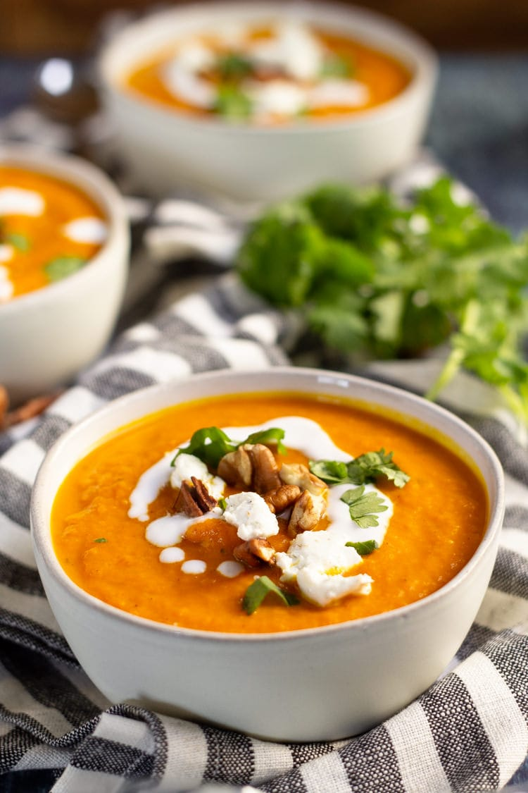 Two white bowls of roasted vegan carrot soup garnished with coconut milk, goat cheese, pecans and fresh parsley