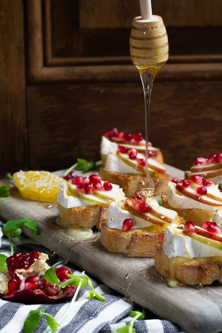 Honey being drizzled over apple brie crostinis loaded with pomegranate