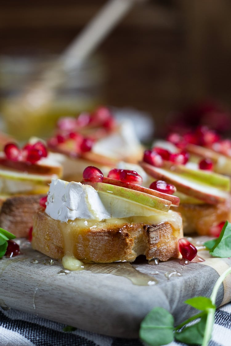 A close up of apple brie crostini garnished with honey and pomegranate seeds