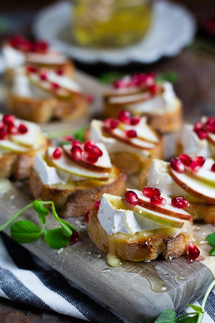 A wooden cutting board serving platter loaded with apple brie crostini garnished with honey and pomegranate seeds
