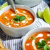 Three white bowls of roasted red pepper and tomato soup garnished with coconut milk and fresh chopped cilantro