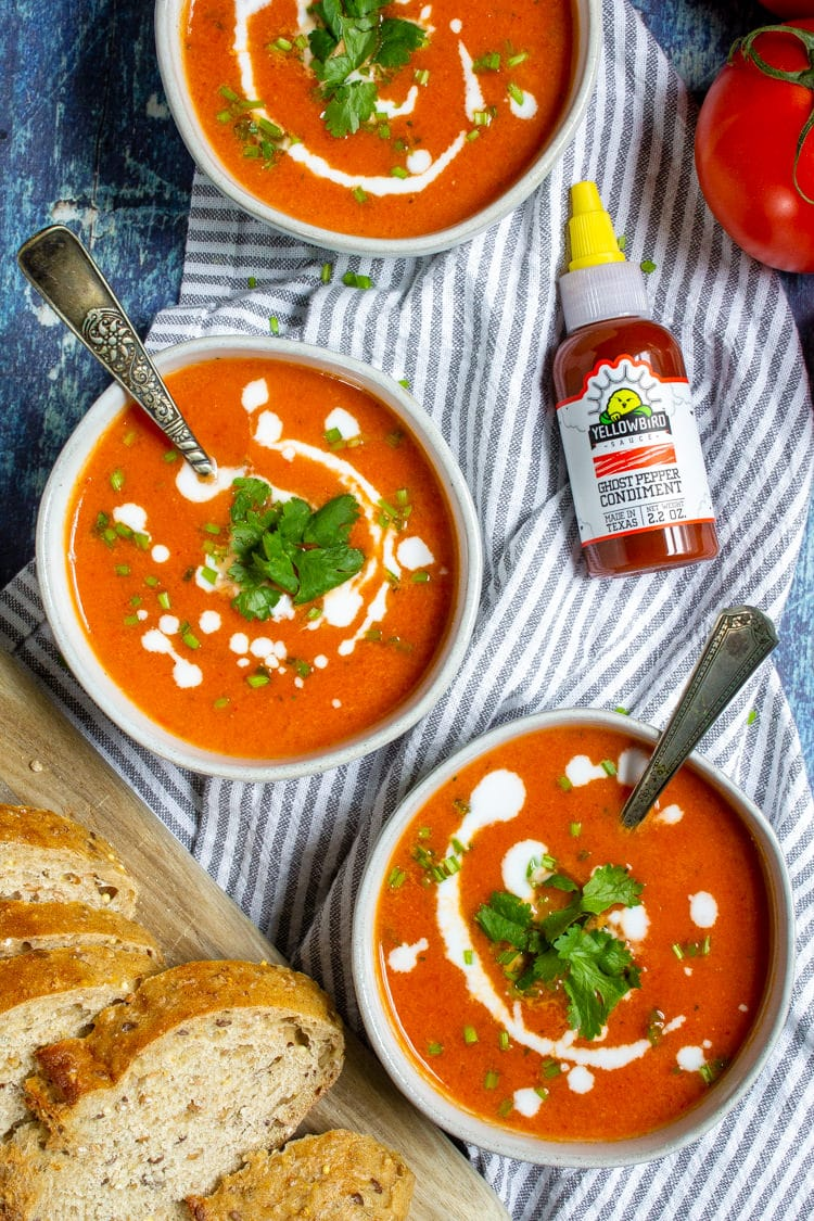 Three bowls of roasted red pepper and tomato soup garnished with coconut milk and cilantro next to a bottle of hot sauce
