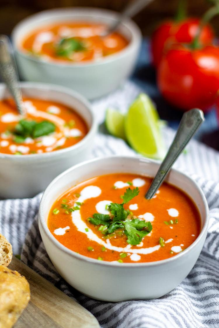 Three bowls of roasted red pepper and tomato soup garnished with a swirl of coconut milk and fresh chopped cilantro