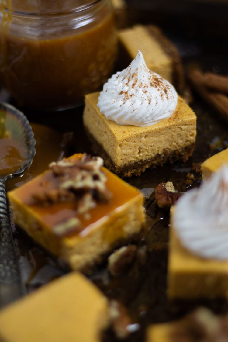 A sheet pan with sliced pumpkin cheesecake bars some garnished with caramel and pecans and some garnished with whipped cream and cinnamon
