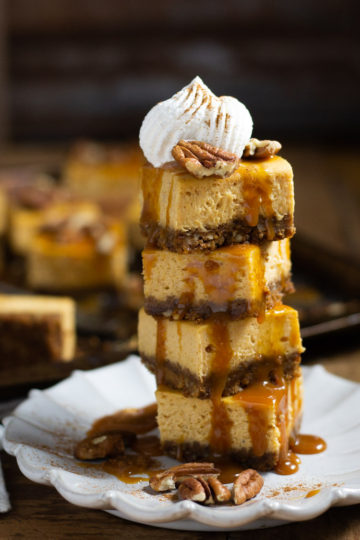 A tower of pumpkin cheesecake bars stacked and drizzled with caramel then topped with pecans and whipped cream