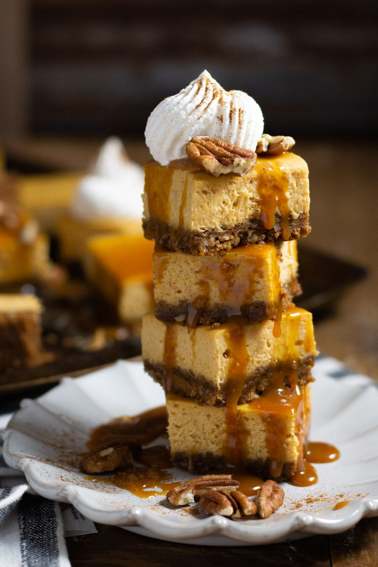 A tower of pumpkin cheesecake bars drizzled with caramel and topped with pecans and whipped cream