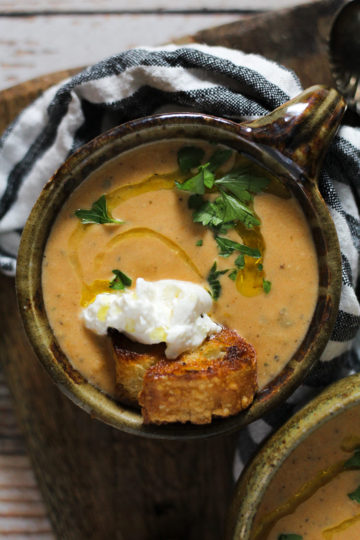 Green ceramic bowl filled with roasted tomato soup garnished with crostini and burrata cheese