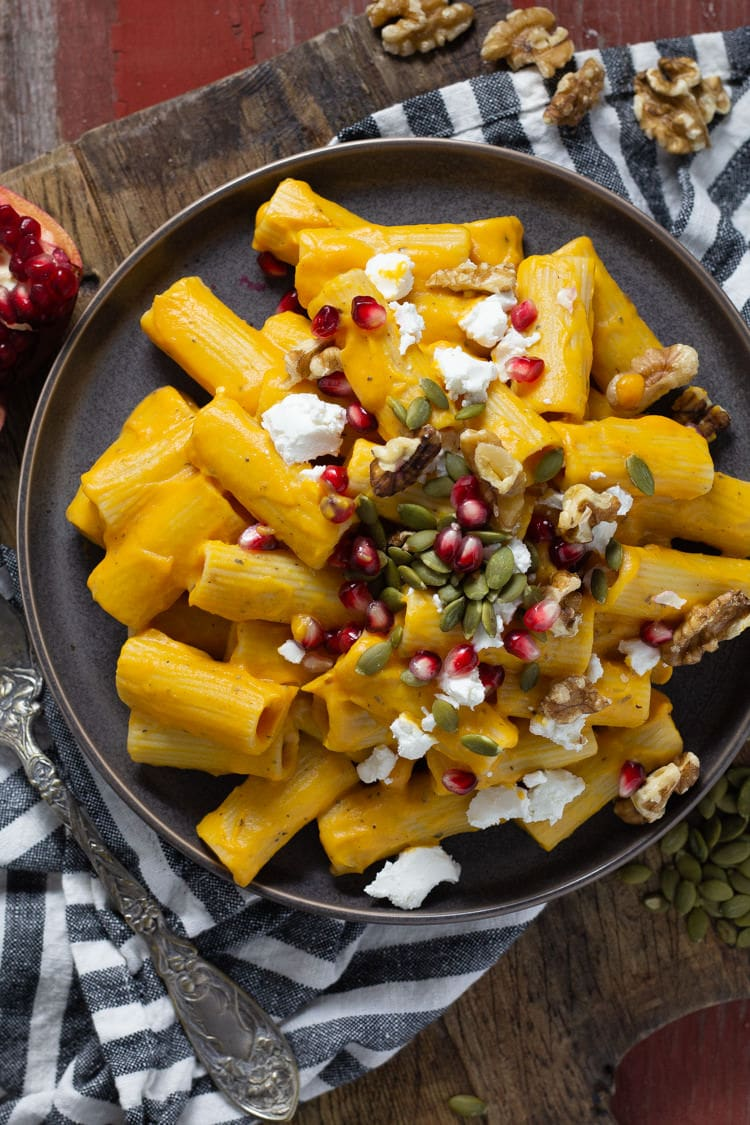 A blue plate filled with roasted butternut squash pasta garnished with goat cheese, pumpkin seeds, walnuts and pomegranate seeds