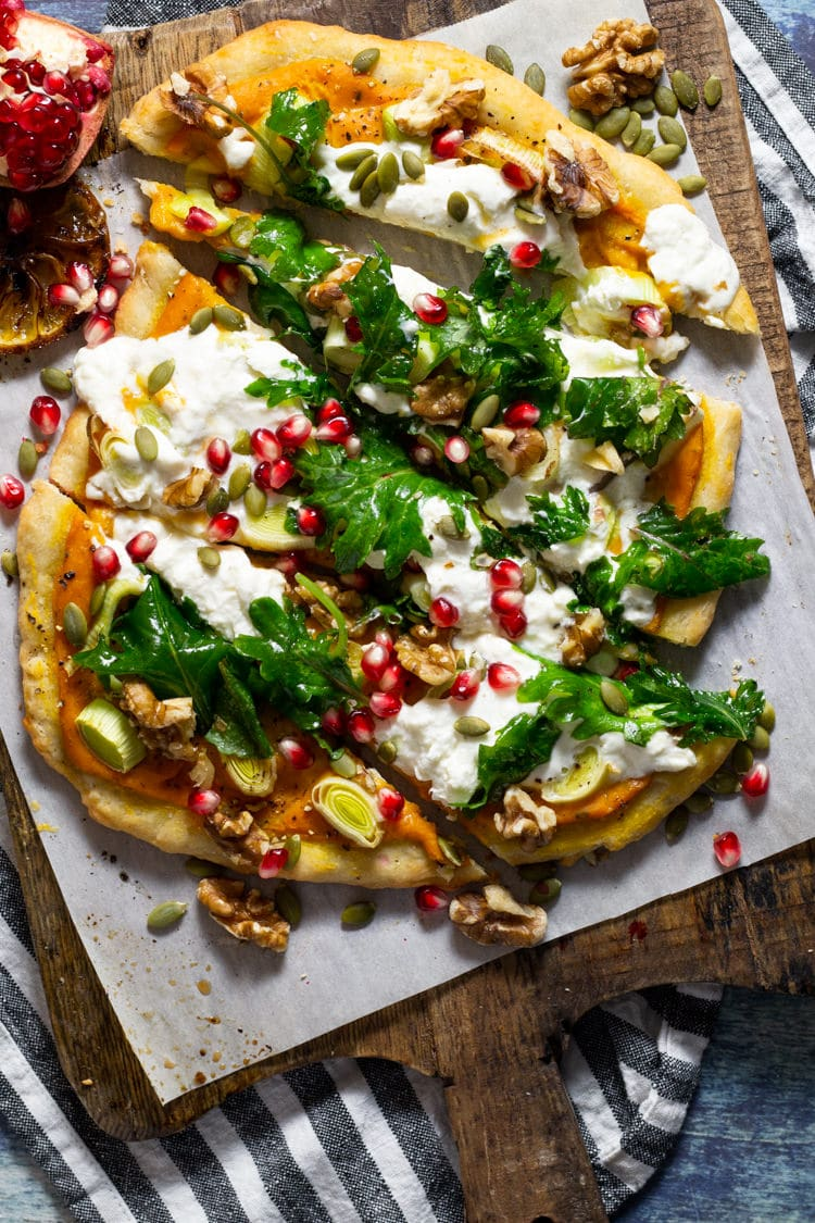 Fall harvest vegetarian pizza loaded with squash cream sauce and creamy burrata cheese cut into slices on a wooden cutting board