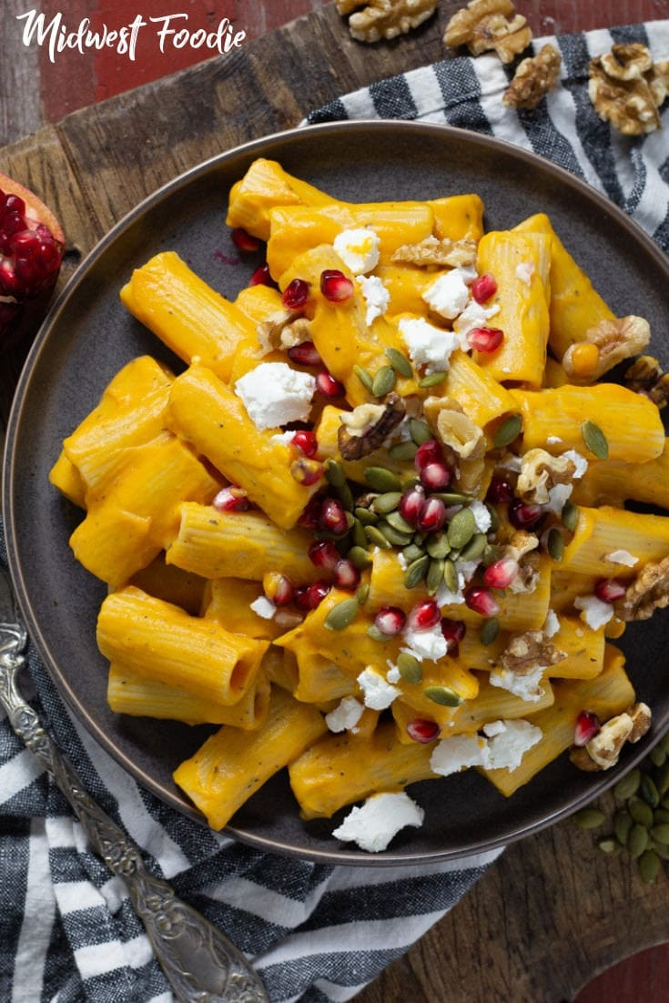 Easy Butternut Squash Pasta -- The quintessential vegetarian Fall dish, this creamy butternut squash pasta is paired with classic flavors of roasted garlic and dried sage. Garnished with seasonal favorites - pomegranate and pumpkin seeds - this vegetarian pasta would be a great addition to your next Sunday night dinner or even a good meat free alternative at your Thanksgiving Day table! #midwestfoodie #vegetarian #familydinner #holiday #easy #recipe