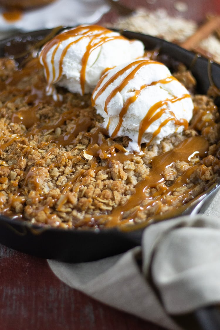 Cast iron pan filled with homemade apple crisp drizzled with caramel and topped with vanilla ice cream