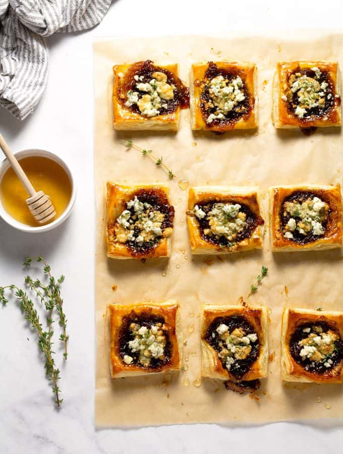 Overhead shot of parchment paper with caramelized onion puff pastry tarts on top of it