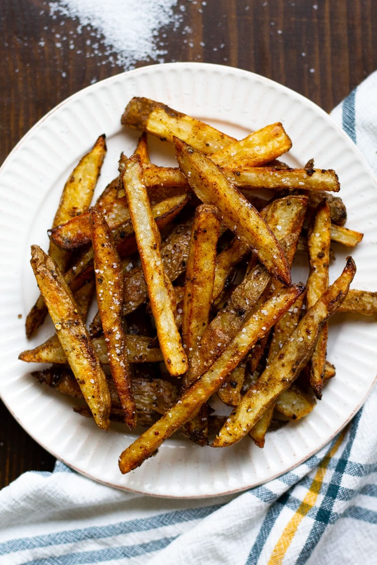 White plate filled with homemade baked french fries