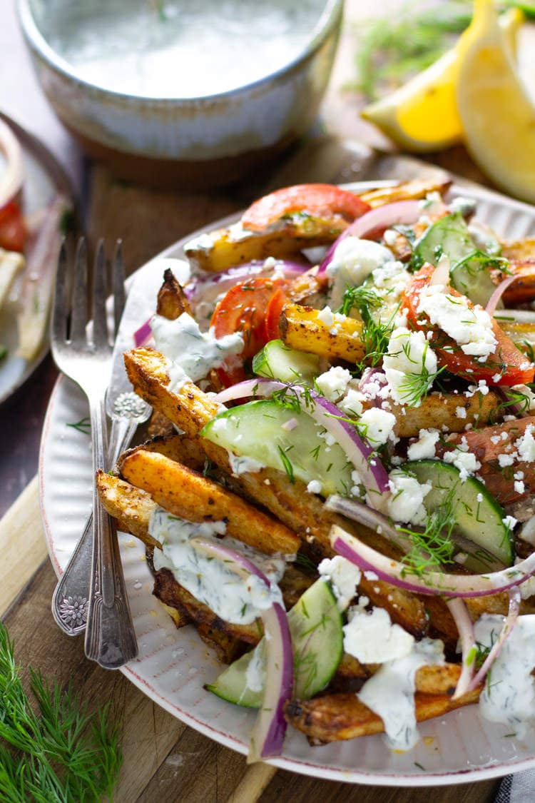 Loaded Greek salad fries on a white plate loaded with veggies feta and tzatziki sauce