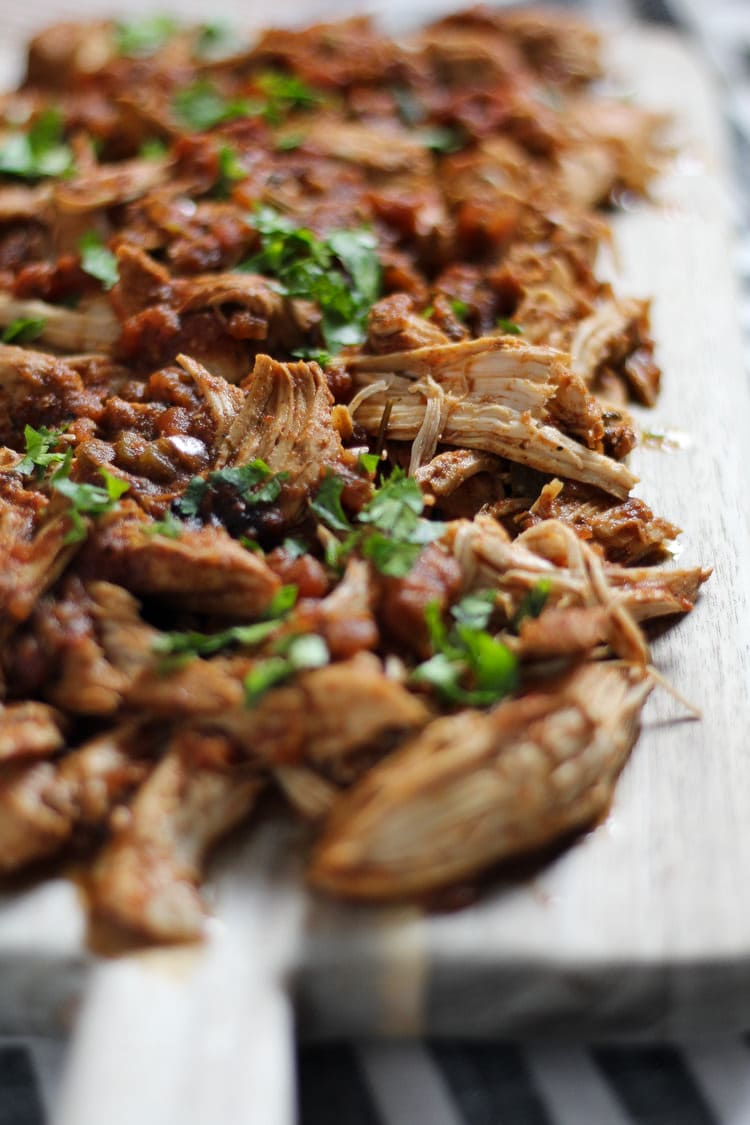 Cutting board filled with slow cooker shredded chicken garnished with fresh chopped cilantro