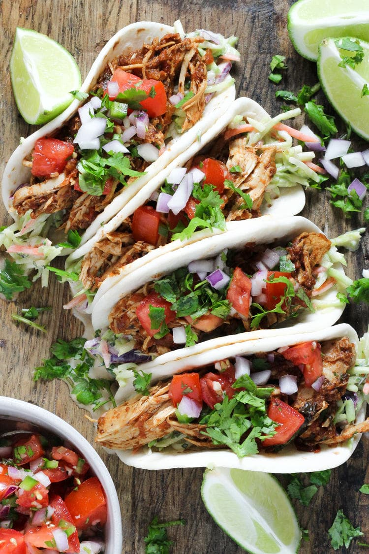 Wooden cutting board filled with slow cooker shredded chicken tacos in flour tortillas garnished with pico de gallo