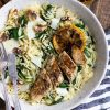 Bowl filled with warm chicken and orzo salad with spinach and grated Parmesan cheese