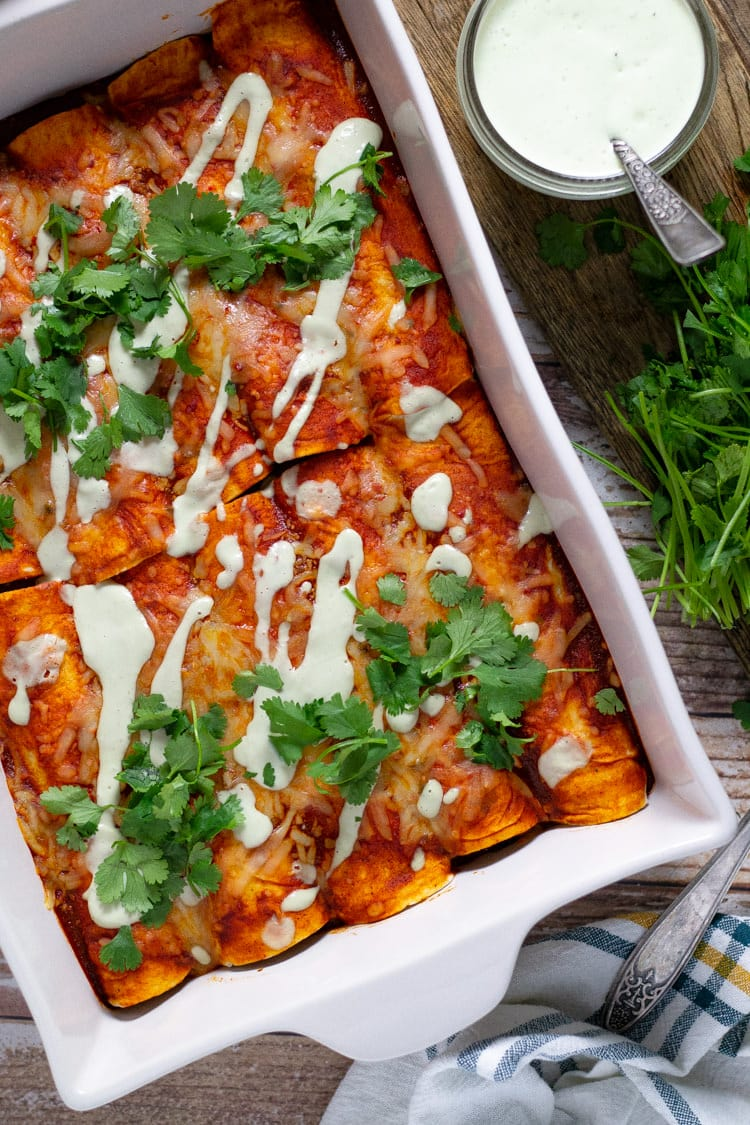 White baking dish filled with beef enchiladas garnished with fresh chopped cilantro