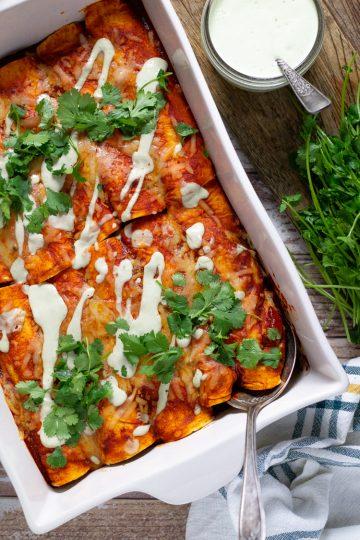 White baking dish filled with beef enchiladas garnished with fresh chopped cilantro