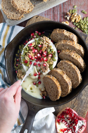 Cast iron skillet filled with sliced multi grain bread with baked brie loaded with walnuts pumpkin seeds and pomegranate seeds