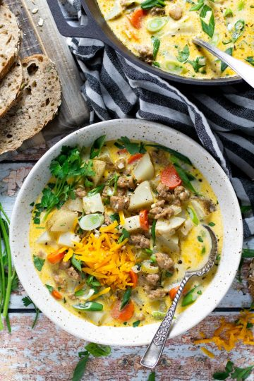 Bowl of sausage and potato beer cheese soup garnished with fresh parsley and green onion