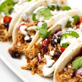 Close up shot of 4 shredded chicken tacos garnished with diced red onion and fresh cilantro