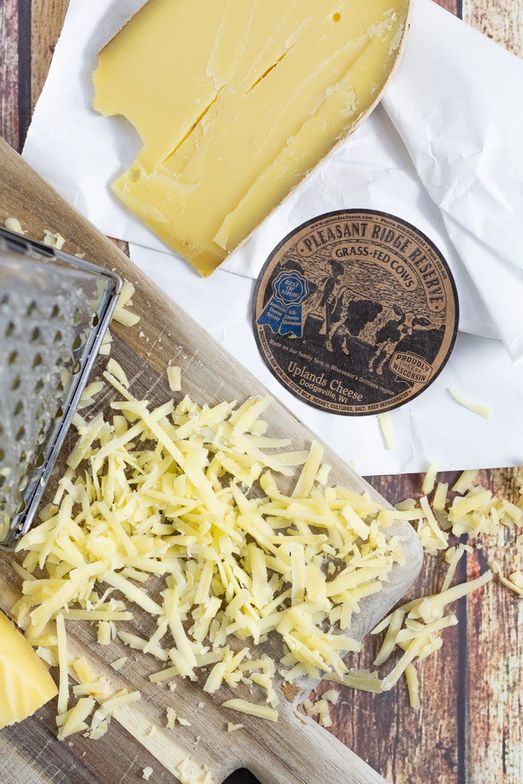 A cutting board with a cheese grater and shredded cheese on a wooden table