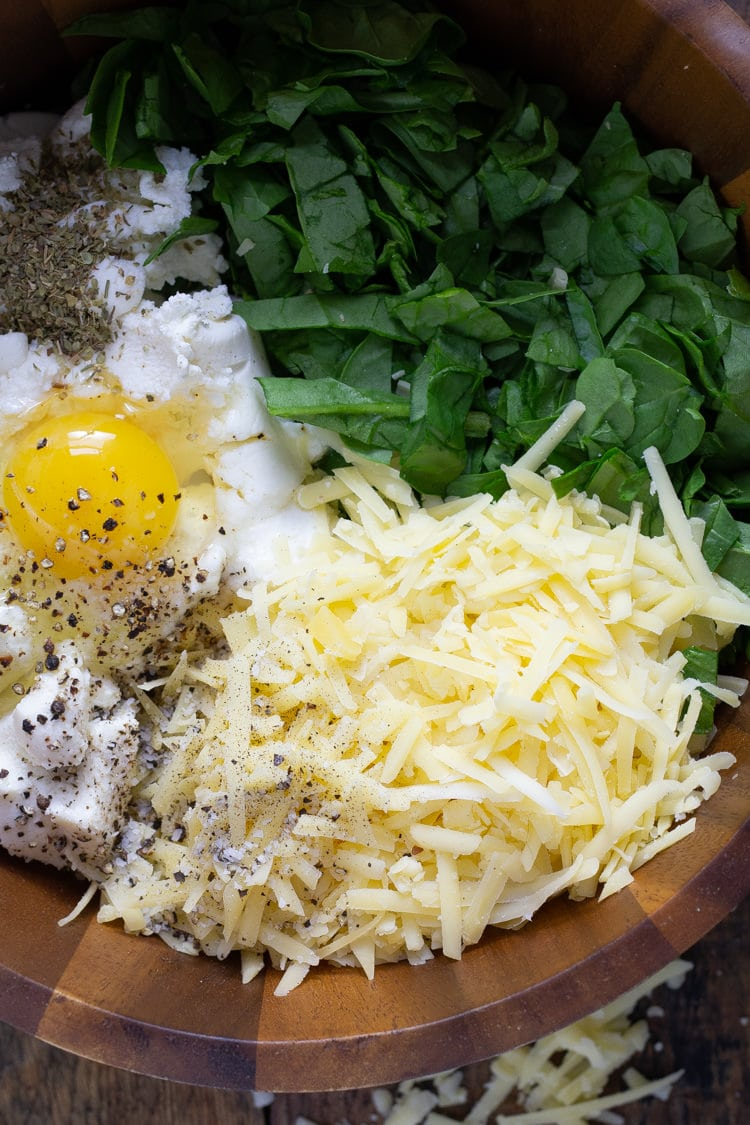 Wooden bowl filled with ricotta cheese spinach and and egg for stuffing the shells
