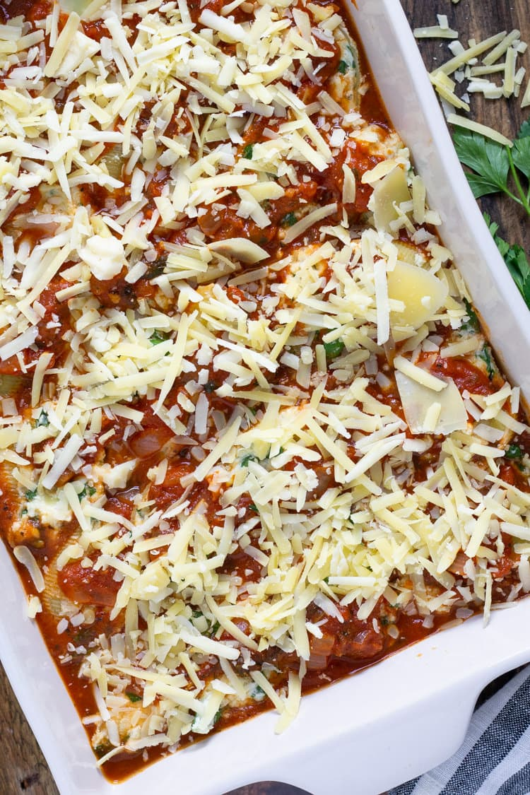 A white baking dish filled with cheese stuffed shells being sprinkled with shredded cheese