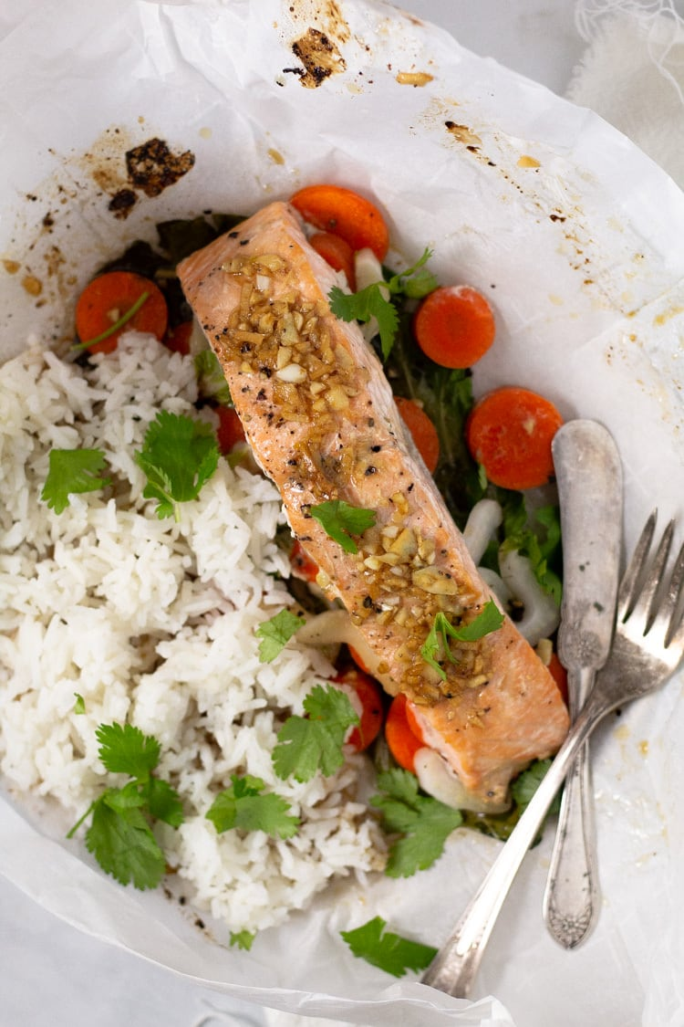 A baked parchment packet salmon with veggies and rice