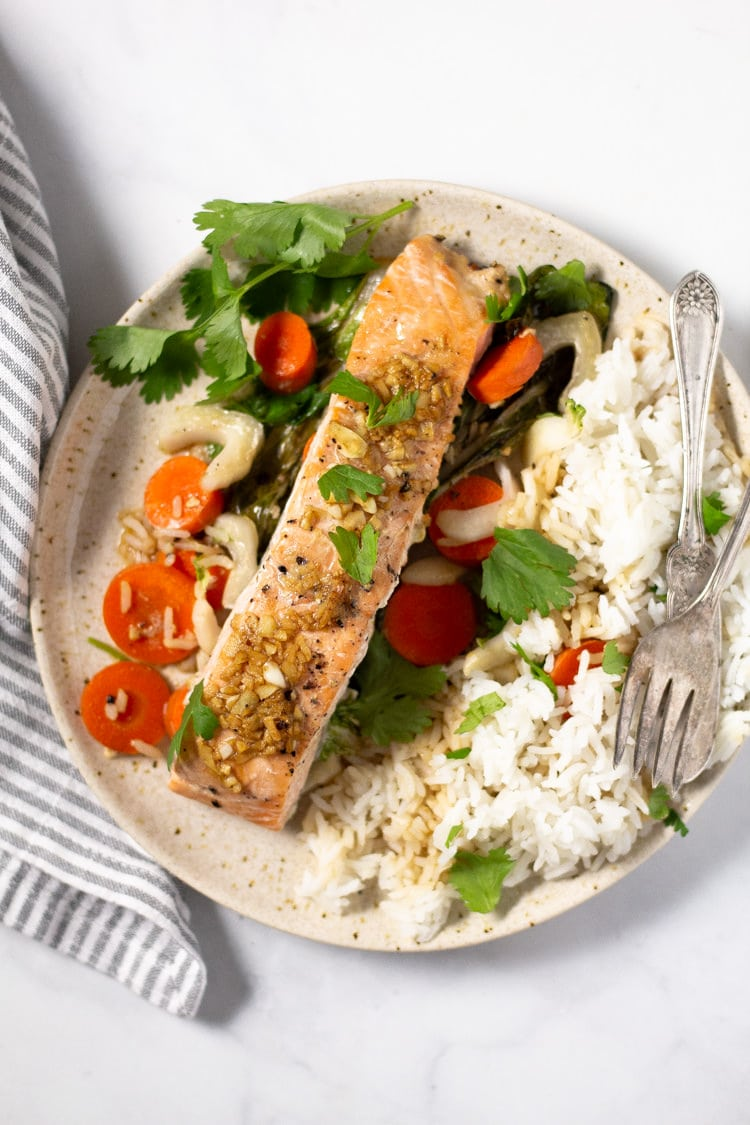 Overhead shot of parchment baked salmon with veggies and rice