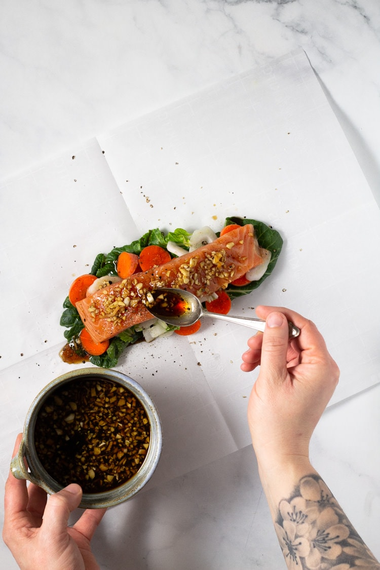 Overhead shot of parchment packet salmon and veggies being drizzled with sauce