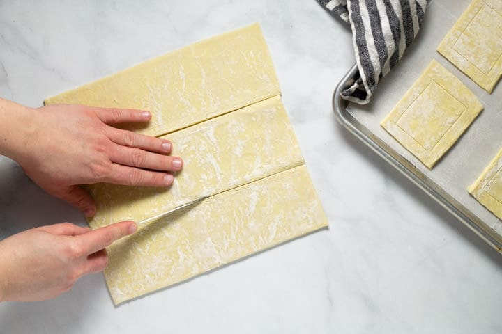 White marble counter top with a sheet of puff pastry being cut into 3 rectangles
