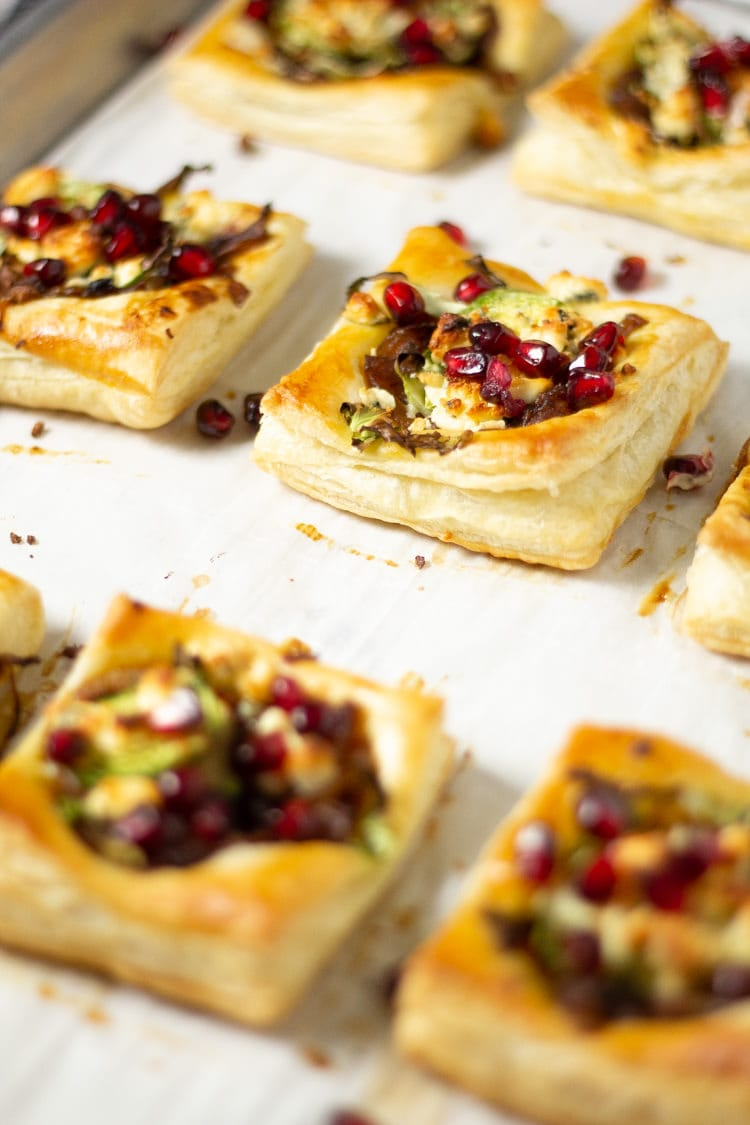 Pan of puff pastry Brussels sprouts tarts topped with pomegranate seeds on a parchment lined baking sheet