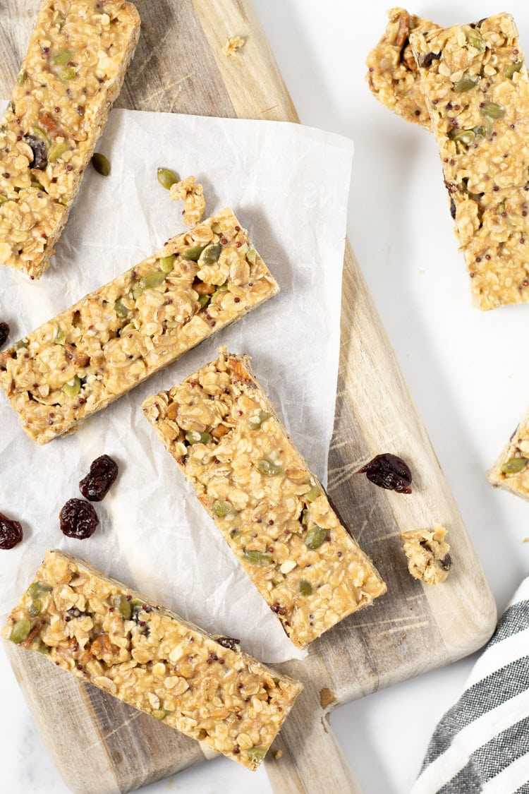 Cutting board with granola bars and dried cherries scattered about